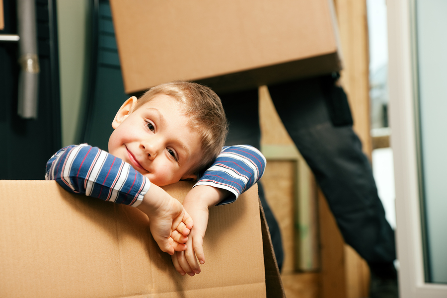 little boy playing in a brown cardboard box